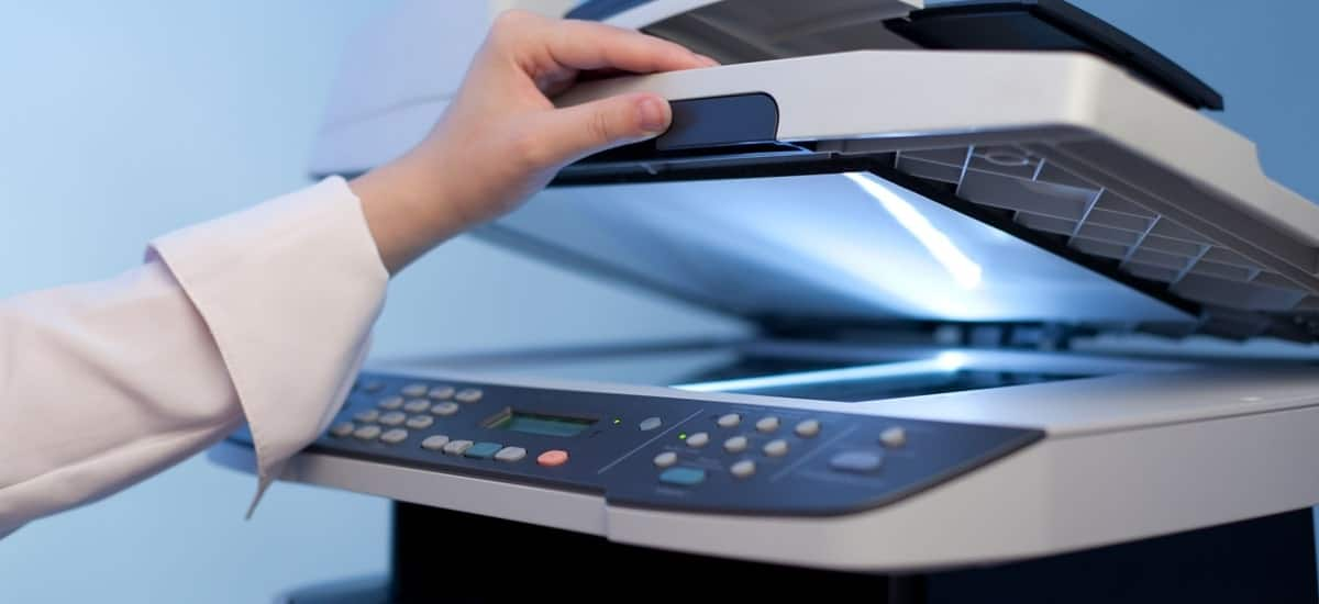 womans arm lifting the scanner on an office multifunction printer